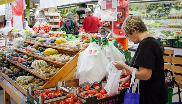 Una dona fa ús d'una de les noves bosses de plàstic reutilitzables.