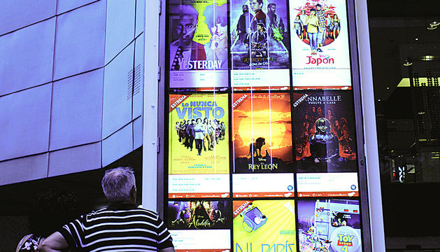 Una parella es mira la cartellera dels Cinemes Illa Carlemany.