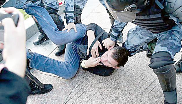 La policia redueix un dels manifestants.