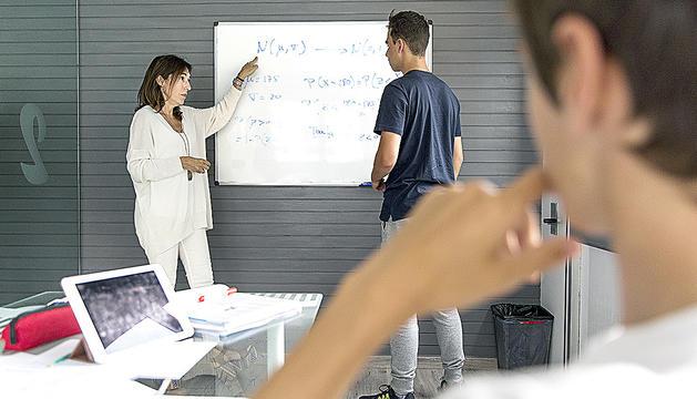 CLASSE DE RECUPERACIÓ de matemàtiques de Mireia Fontova a dos alumnes que han suspès l'assignatura de primer de batxillerat.