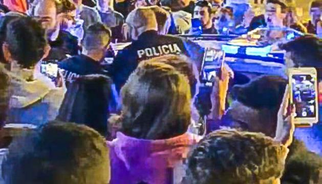 Els agents, rodejats de joves, introduint un dels detinguts al vehicle policial.