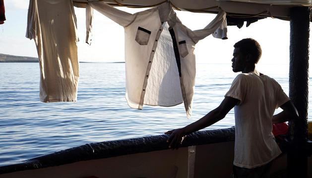 Un migrant mirant des de la coberta del buc Open Arms les costes de Lampedusa.