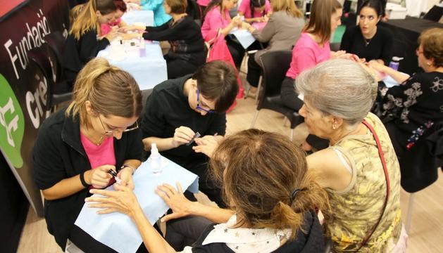 Un grup de padrines es pinten les ungles durant les activitats del XI Saló de la Gent Gran