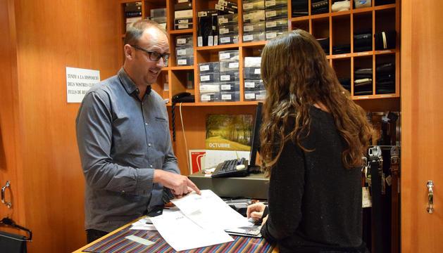 Un botiguer de la Seu explica a una clienta com omplir el formulari de devolució.