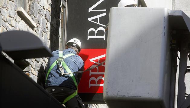 Retirada del cartell de BPA de la seu central del banc.