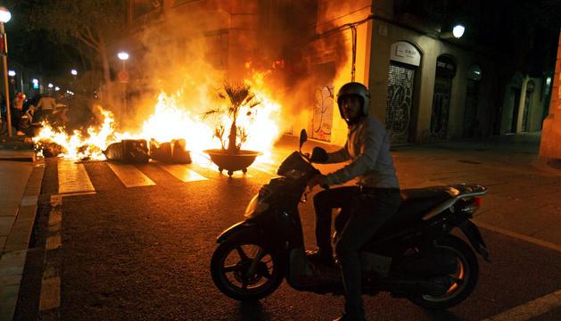 Un motorista es troba amb una barricada de foc a la Rambla.
