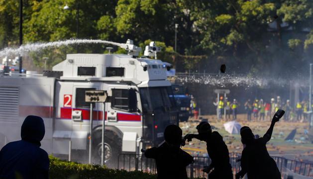 Els manifestants llançant pedres al camió amb el canó d'aigua.