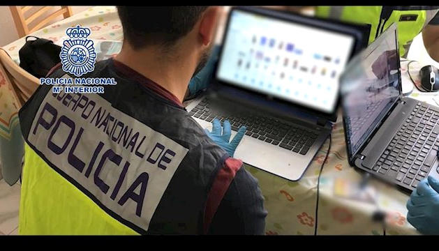 Un agent de la policia espanyola amb un ordinador intervingut, en una imatge d'arxiu.