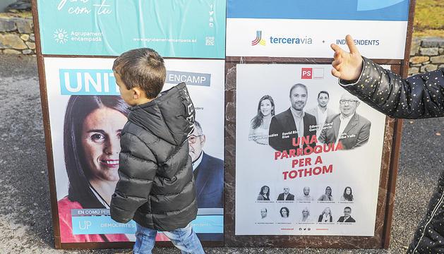 Infants al costat d'uns plafons amb els cartells electorals, a Encamp, ahir.