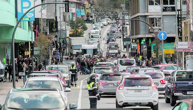 Cues de cotxes i vianants al carrer de la Unió.