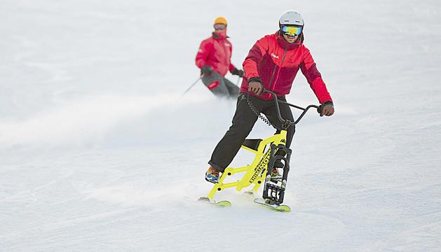Un usuari baixant amb una de les bicicletes de neu, les 'snow trike'.