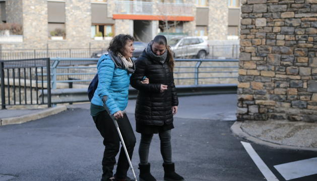Cristina Garcia, usuària del Servei d'Atenció Domiciliària, passejant amb una de les professionals del servei