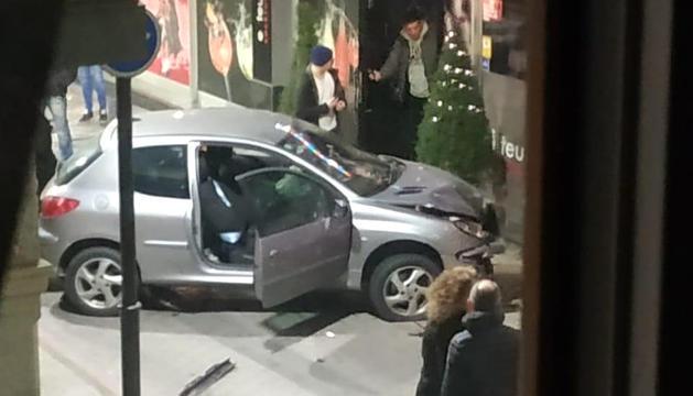 El vehicle després d'impactar contra la façana del local.