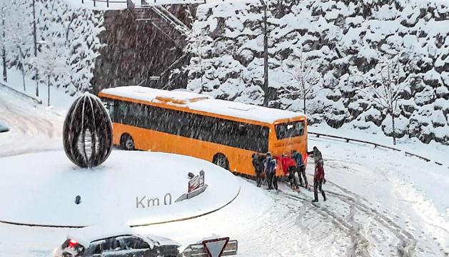 Un grup de persones i usuaris del servei de transport públic empenyent un autobús de la línia interurbana a la rotonda del quilòmetre zero.