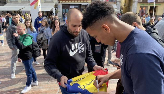 Tyson Pérez signant una samarreta tricolor.