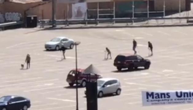 Quatre joves surten amb el patinet a l'aparcament del Parc Central