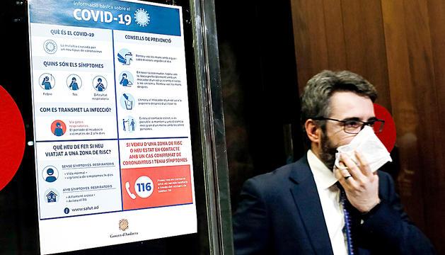 El ministre portaveu,Eric Jover, amb una mascareta i un dels cartells de mesures contra la Covid-19.