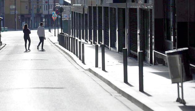 Una parella en un carrer d'Andorra la Vella buit pel confinament de la població.