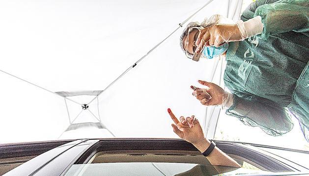 Una voluntària realitzant el test d'anticossos a una dona en el seu vehicle.