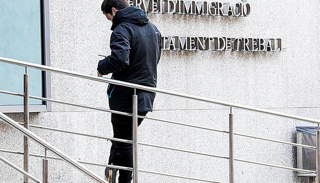 Un home esperant el torn davant de l'edifici administratiu del departament de Treball.