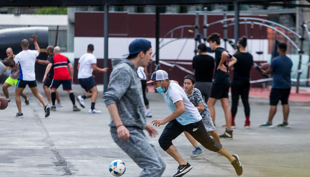 Un grup de joves jugant a futbol i a bàsquet a la plaça del Poble d'Andorra la Vella, ahir.