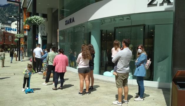 Clients espereant per entrar a una botiga de ropa