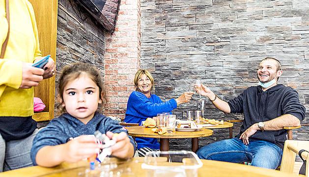 Una nena en una taula i dos turistes dinant al restaurant de l'hotel Les Neus.