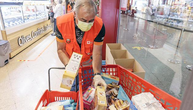 Un voluntari organitzant les donacions en un centre comercial.