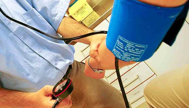 Un metge mesurant la pressió a un pacient.