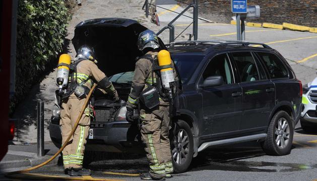 Els bombers amb el cotxe que s'ha incendiat