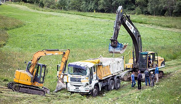 Dues excavadores al costat del camió que es va accidentar ahir al camí de la Ruta del Ferro.