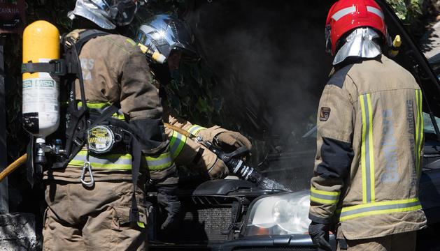 Els bombers actuant en el petit incendi en un cotxe a l'Avinguda del Pessebre
