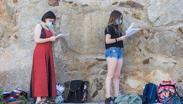Dues estudiants repassant els darrers apunts abans d'examinar-se.