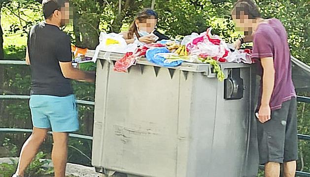 Un grup de joves, possiblement temporers, recollint aliments d'un contenidor d'un supermercat d'Encamp.
