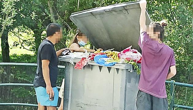 Els joves rebuscant dins del contenidor.