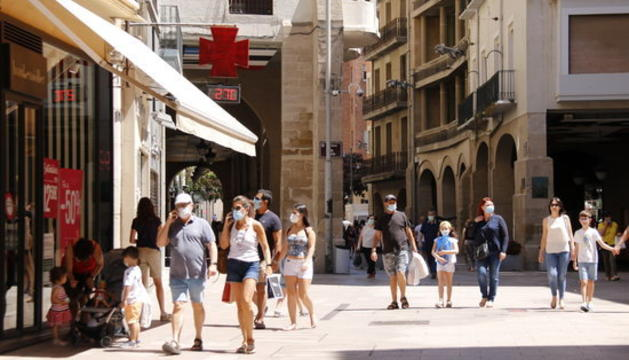 Diverses persones passejant amb mascareta per l'Eix Comercial de Lleida, a l'alçada de la plaça de la Paeria en el primer diumenge de rebaixes .