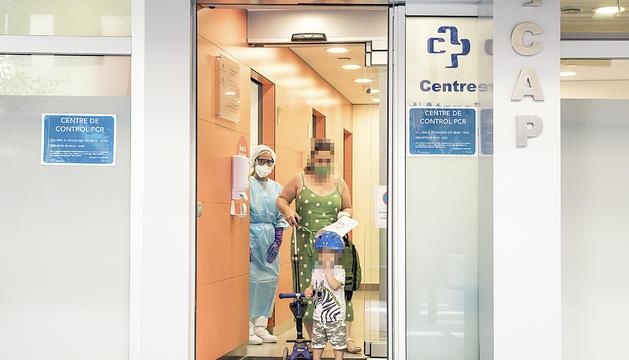 Una dona i un nen surten del punt que s'ha habilitat al CAP de la Sardana per fer proves de detecció de la Covid-19.