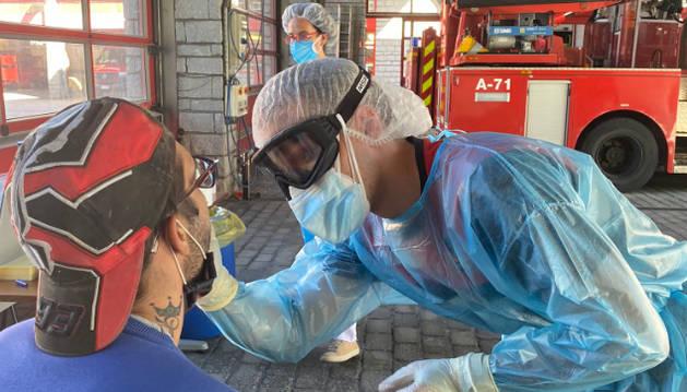 Un sanitari extreu una mostra a un ciutadà que s'ha fet la prova aquest matí a la caserna.