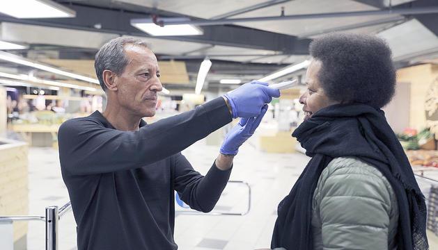 Un treballador pren la temperatura a un consumidor.