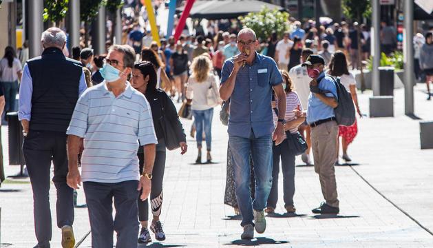 Turistes a l'eix comercial de la capital.