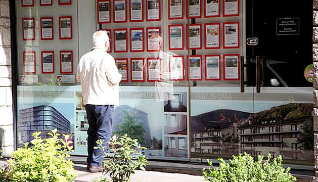 Una persona mirant els anuncis d'una immobiliària des de l'exterior.