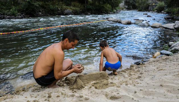 Un pare i un fill jugant amb la sorra, ahir a la tarda.
