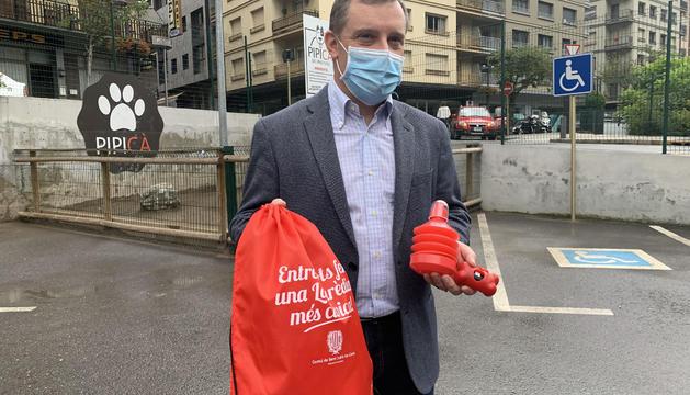 Josep Majoral mostra la bossa, l'ampolla d'aigua i l'estoig de bosses que regala el comú