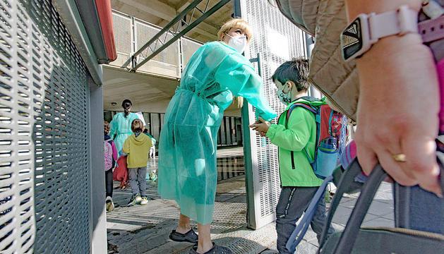 Una professora acompanya un infant a l'entrada de l'escola.