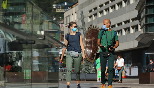 Dos visitants passejant pel centre d'Andorra la Vella.