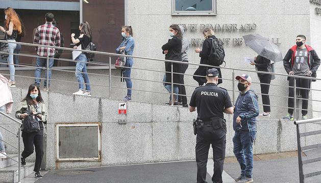 Grups de temporers fent cua a les oficines d'immigració.