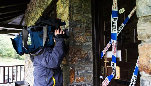 Un càmara de televisió pren imatges de l'entrada del pis on s'ha comés el crim