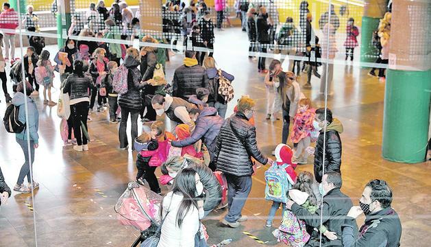 Infants i famílies a l'entrada de l'escola amb mascareta.