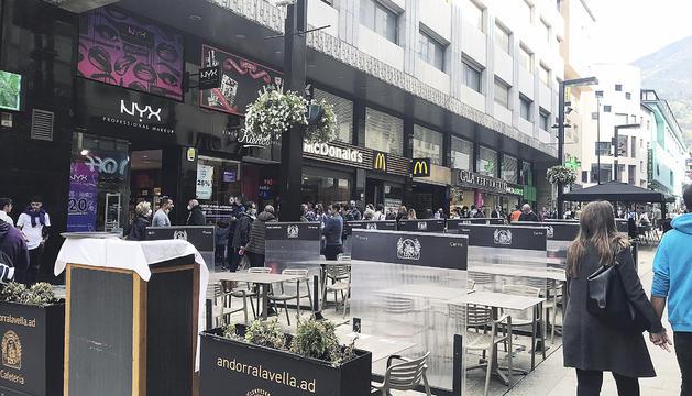Una allau de turistes a l'avinguda Meritxell passen per la terrassa buida d'un bar.