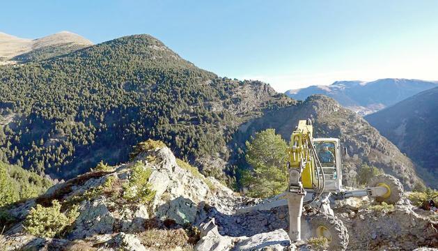 Una màquina treballant a la zona on s'ha d'instal·lar el pont tibetà.